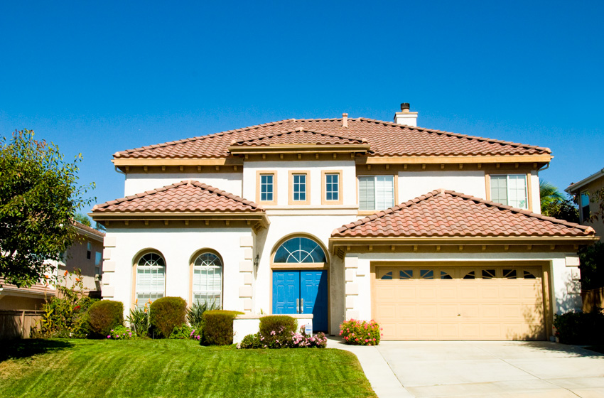 Large house spanish style front lawn blue exterior door garage