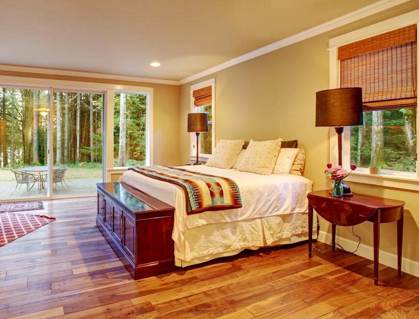 Large master bedroom with hardwood floor and sliding glass door to backyard