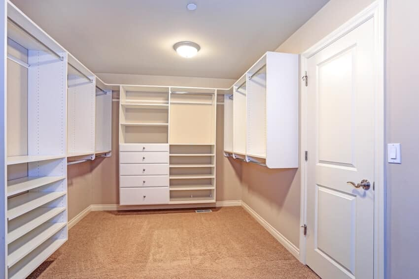 A large walk in closet lined with built in drawers clothes rails and shelving over light brown carpet floor