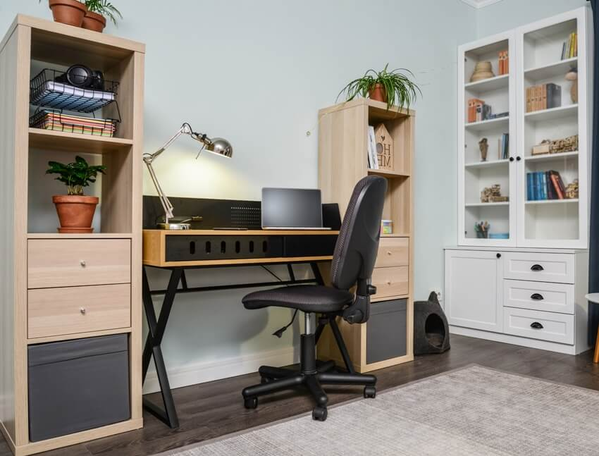 A light cozy teen room with white bookcase with drawers a working desk and laptop on it