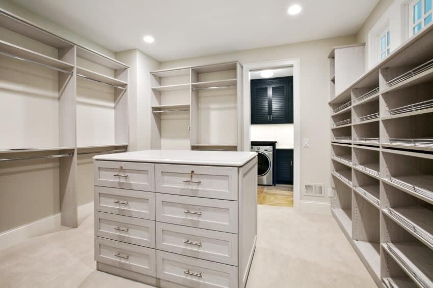 Light gray interior of a spacious walk in closet with an island dresser
