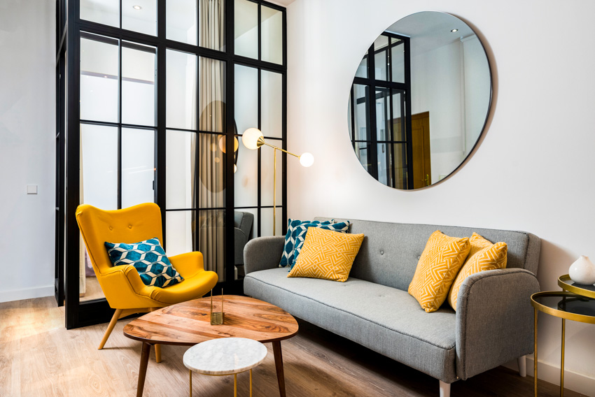 Living room round mirror on wall sofa with pillows glass window