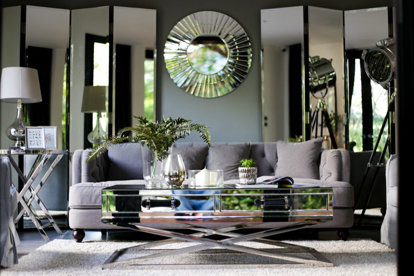 Living room space with multiple mirrors on wall sofa chairs