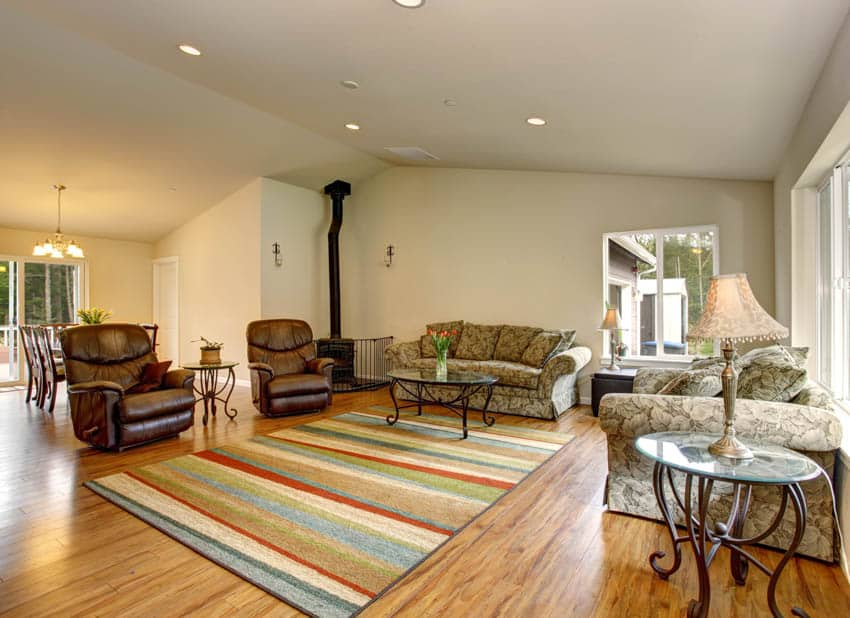 Living room with brown leather recliners colorful rug table lamp white walls
