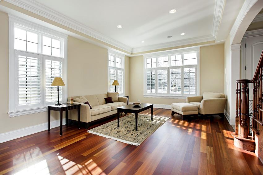 Living room with cherry wood flooring sofa chairs windows