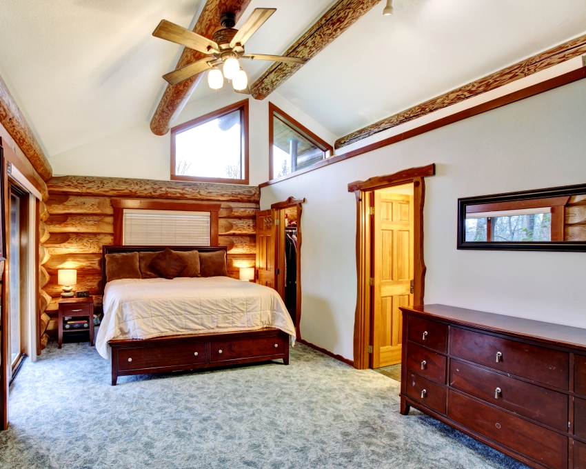 Log cabin bedroom under pitched ceiling with cherrywood furniture set