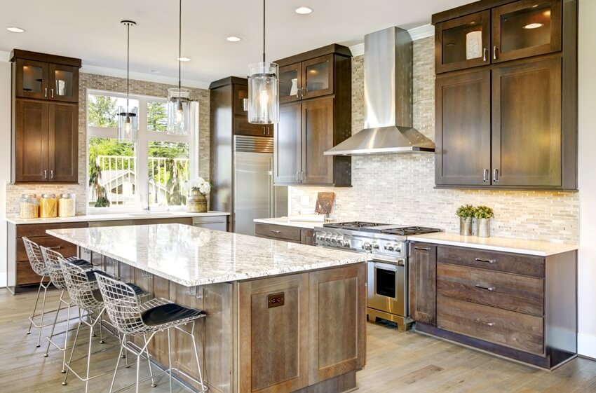 Luxury kitchen accented with large granite kitchen island taupe tile backsplash natural brown wood cabinets and lots of natural light