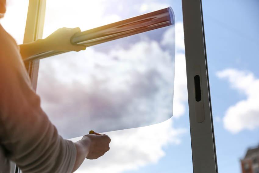 Man applying tint on bathroom window