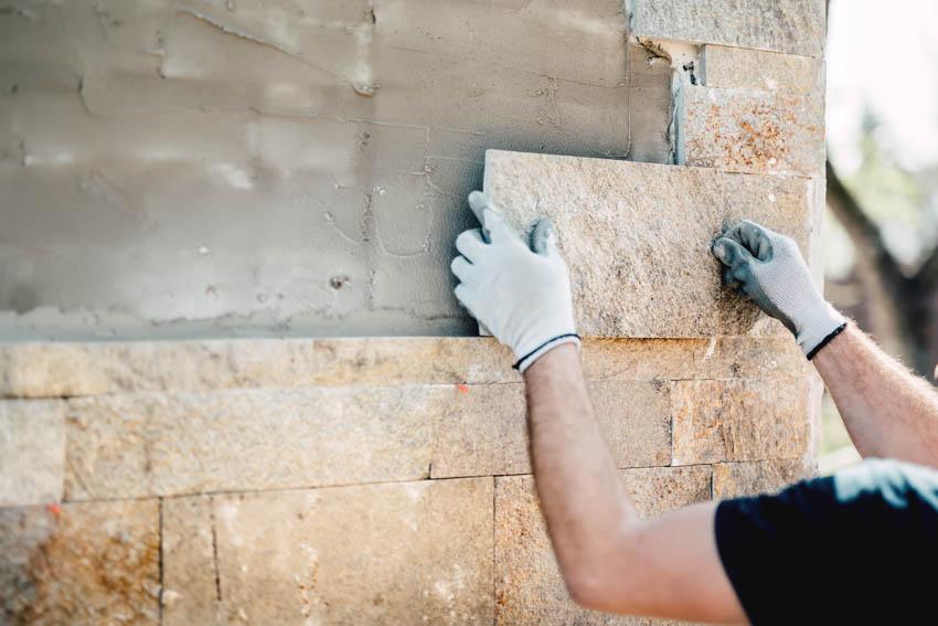 Man installing travertine tiles on wall