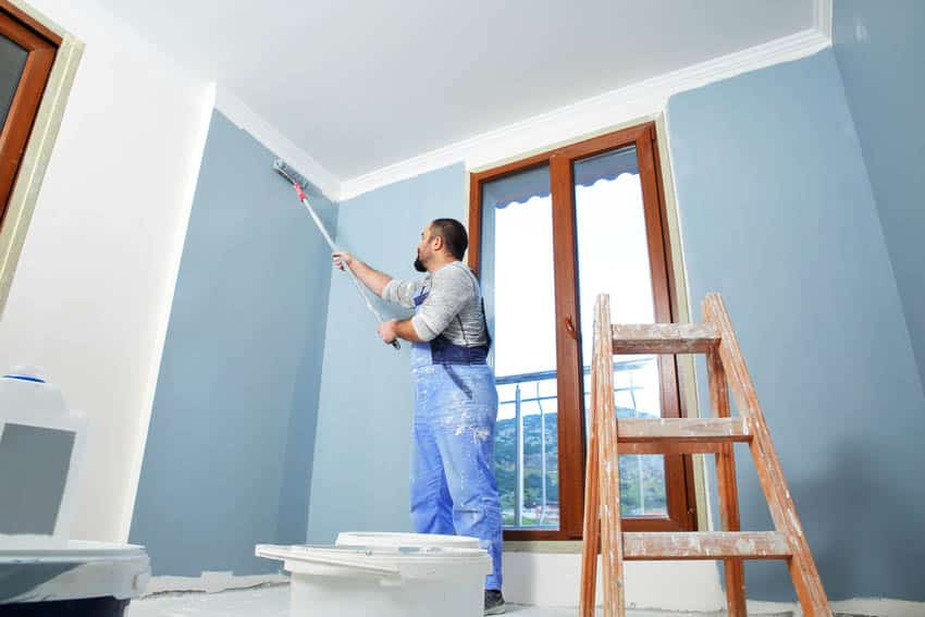 Man painting room with light blue paint