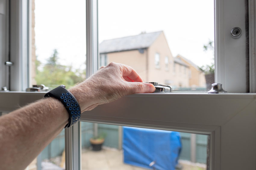 Man unlocking double hung window with swivel action lock