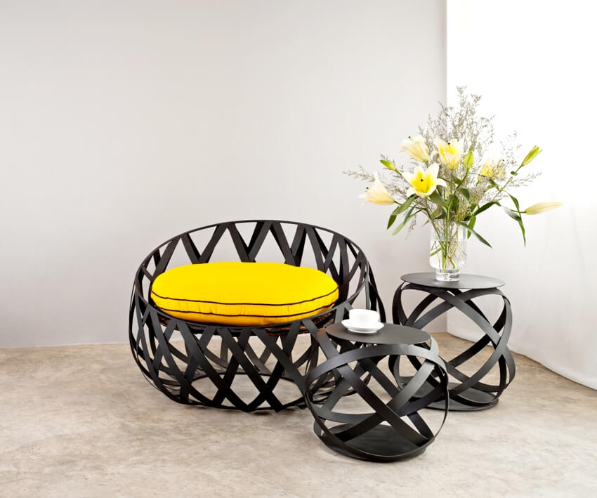 Metal sofa with black paint and yellow pillow with lily flowers on metal table