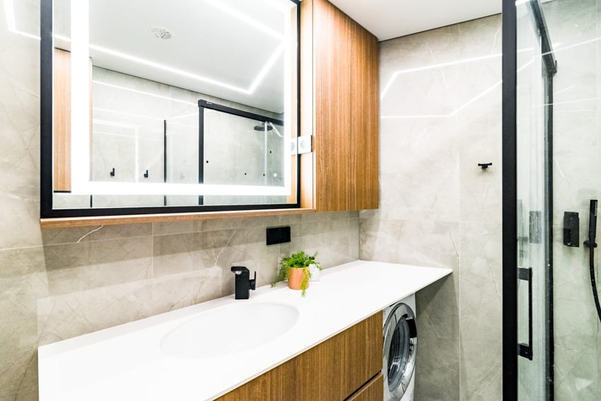 Mirror inside gray bathroom with wood cabinets