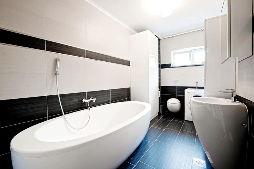 A modern bathroom with black and white tiles a bathtub sink and washing machine