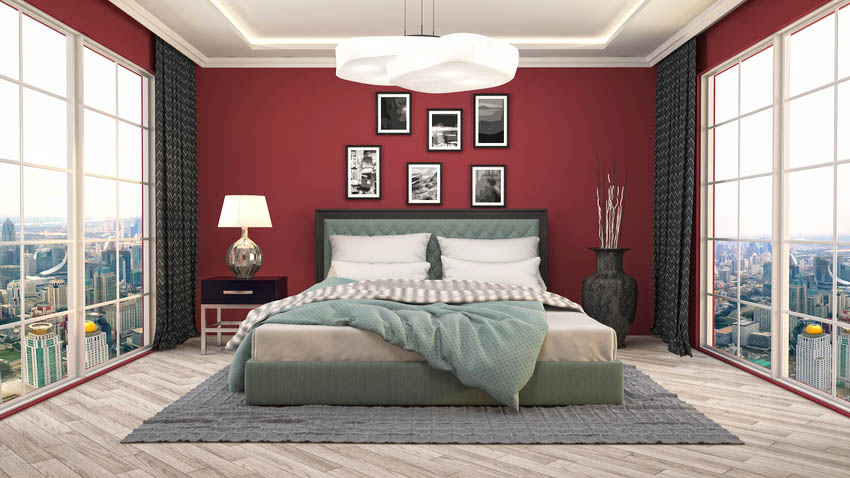 Modern bedroom interior with red walls floor to ceiling windows and laminate flooring