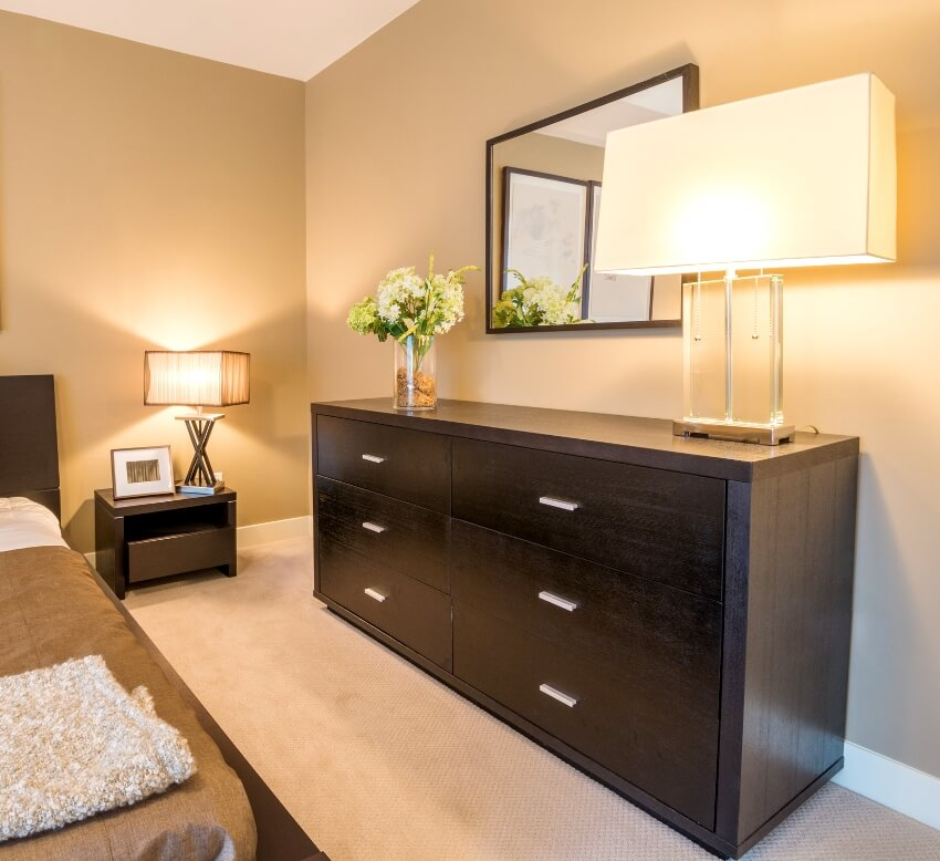 Modern bright bedroom interior with a contemporary dresser and mirror