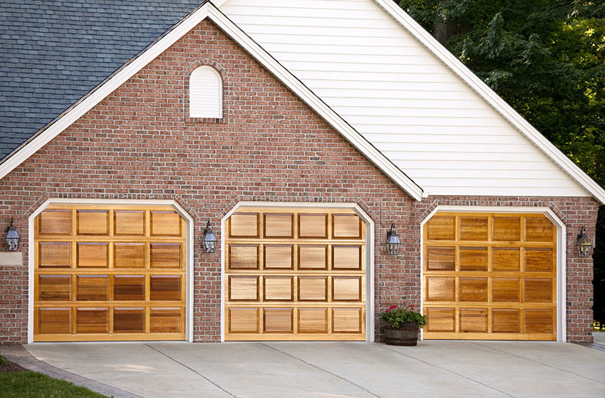 Modern garage with brick and vinyl sidings and wood doors