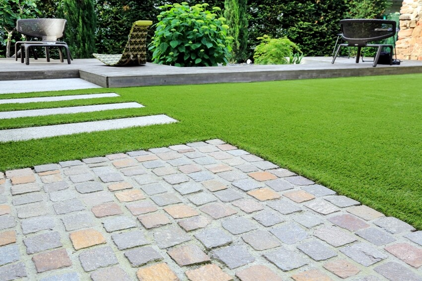 Modern garden design and terrace construction with a material mix of belgian cobble paving stones and concrete paving slab and artificial lawn and wood
