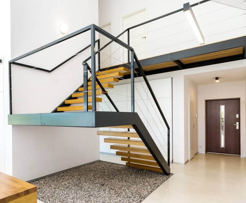 Modern house interior with massive staircase of black metal and wood and space filled with pebbles underneath