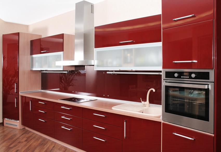 Modern kitchen interior with wooden flooring red door and kitchen cabinets