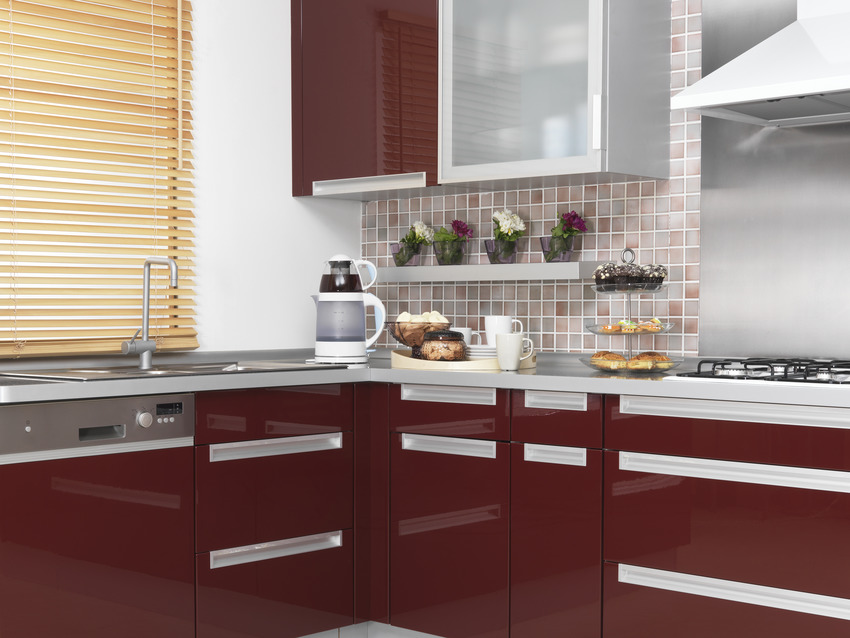 Modern kitchen with red acrylic cabinets and stainless steel sink