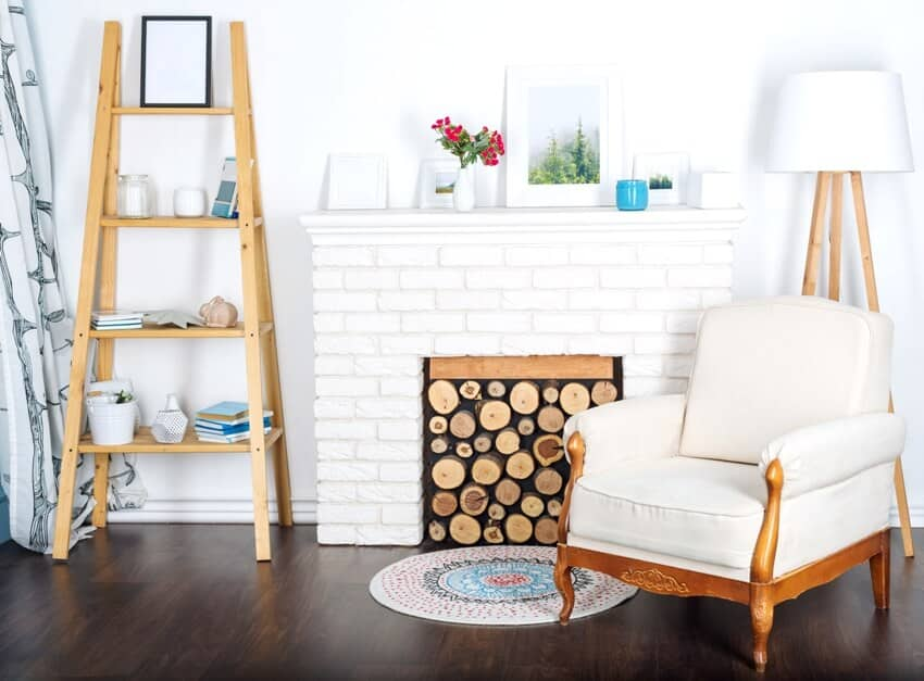A modern light interior with fireplace a cozy white armchair and a leaning bookshelf