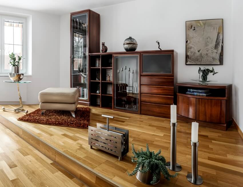 A modern spacious library in cool style with a variety of decorations wooden with glass bookcase and wooden floors
