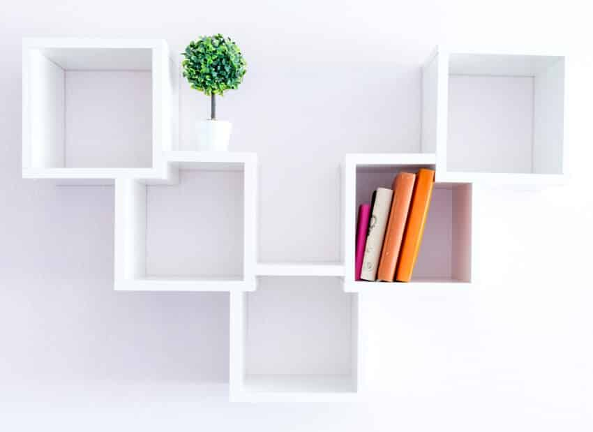 A modern white modular bookshelf on a white wall with a pair of books and a flower