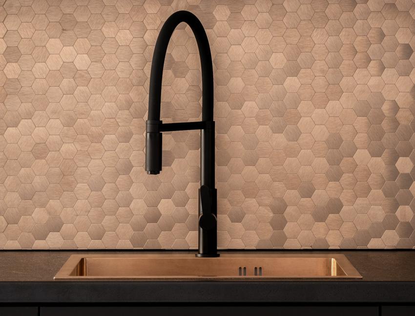 Mosaic tile pattern backsplash black countertop faucet