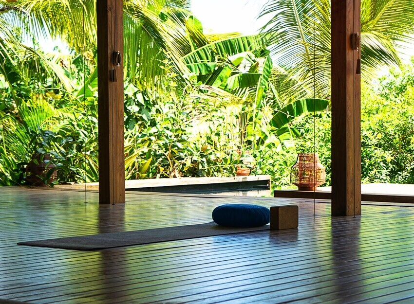 An open tropical yoga studio place with view outside to the beautiful garden with palm trees