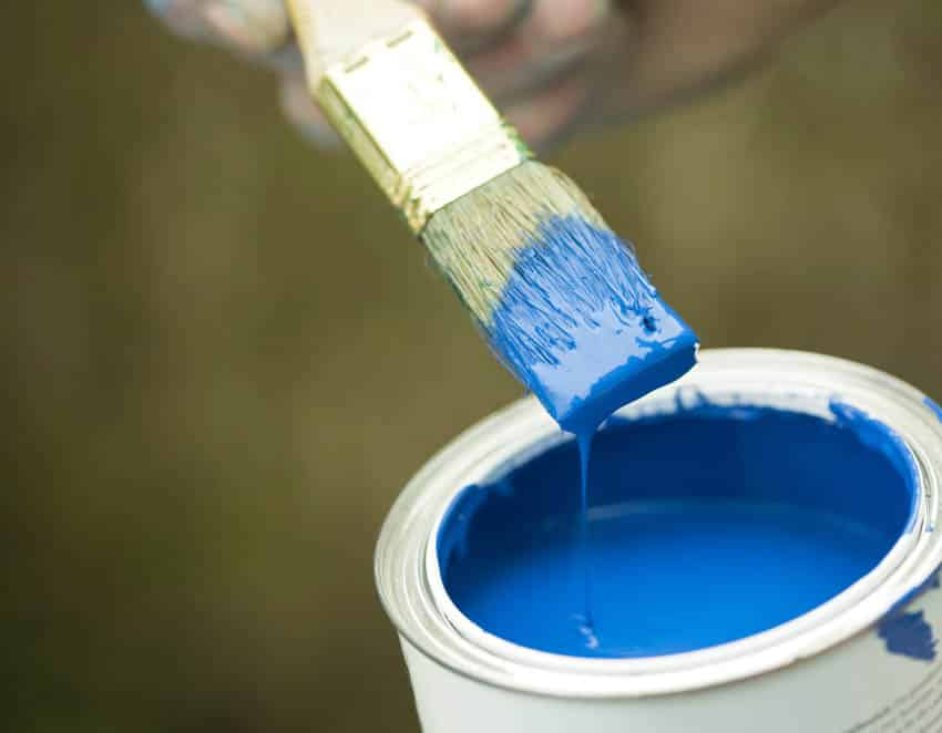 Opened can of blue paint with paint brush