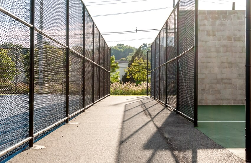 Outdoor sports and fitness area with black chain link fence