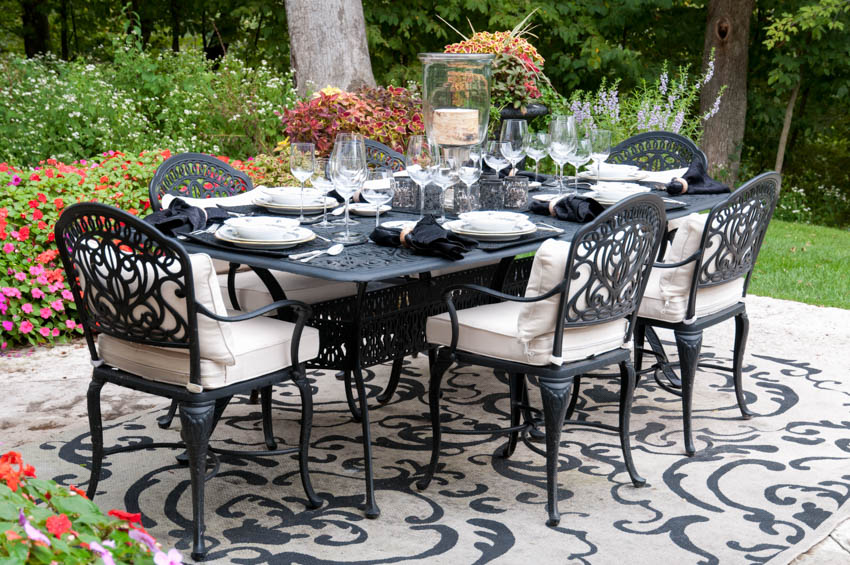 Outdoor table and powdercoated chairs on rug backyard