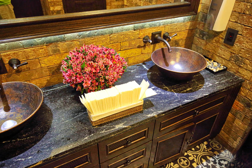 Pair of sinks made of copper on top of wooden drawers