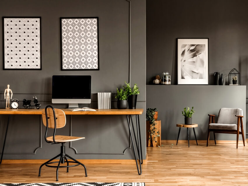 Patterned framed posters on the wall above desk with computer monitor in grey home office interior