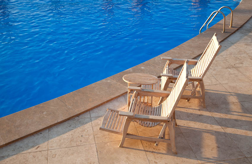 Pool side made of travertine with lounge chairs and small table
