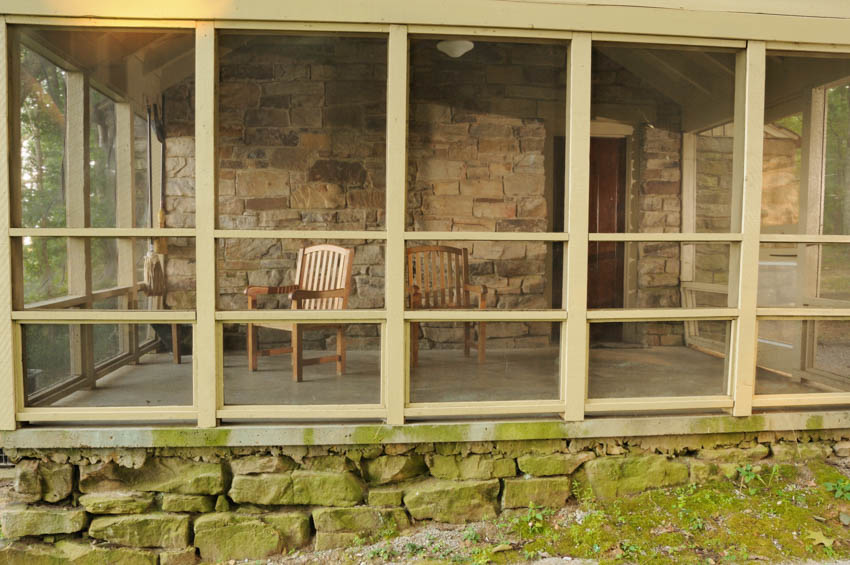 Porch transformed into a room with chairs brick wall tall glass windows