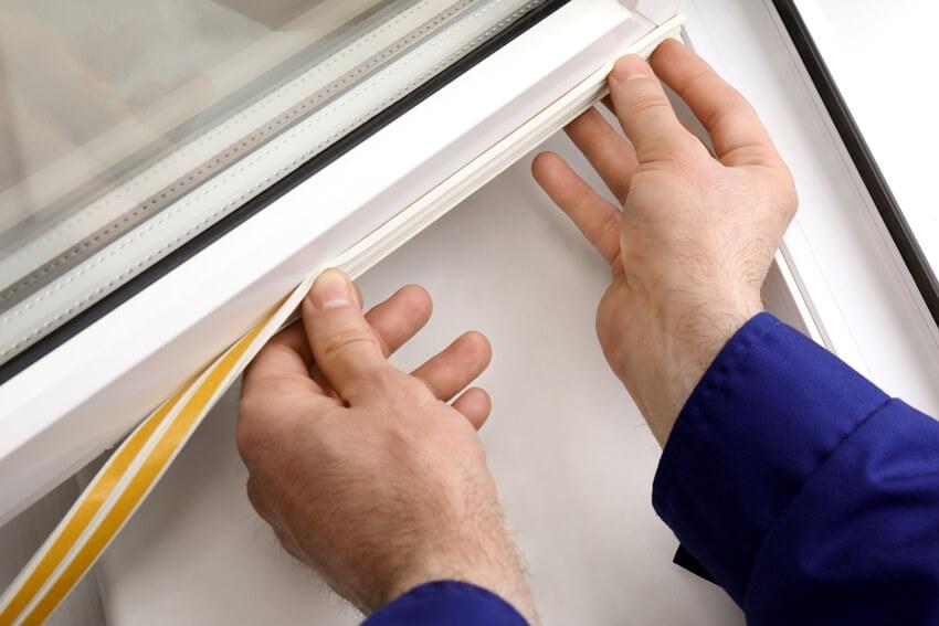 Putting foam strip onto window indoors