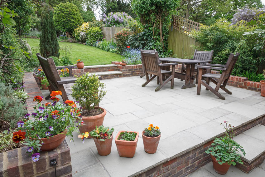Raised patio in backyard with wood table chairs foilage