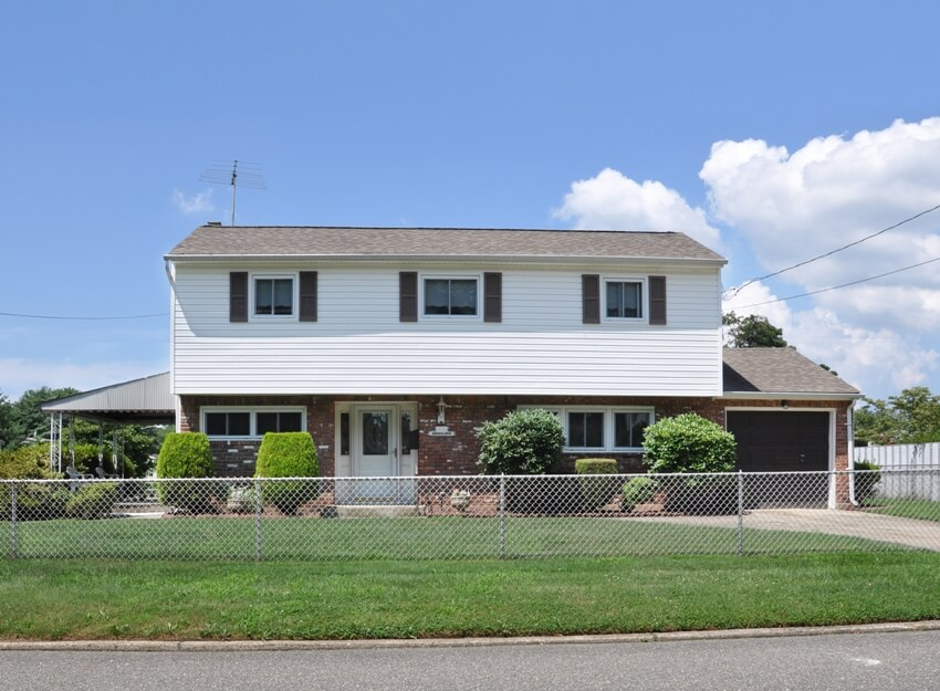 Residential home with siding and brick chain link fence and a landscaped front yard lawn