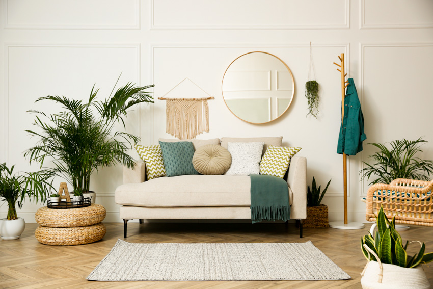 Round mirror above sofa chair rug potted indoor plants