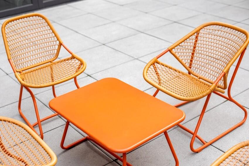 Set of orange painted patio furniture around a metal coffee table
