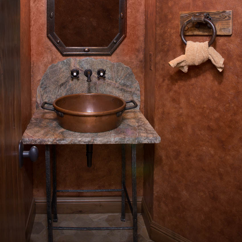 Small bathroom space with rustic copper sink mirror and red wall