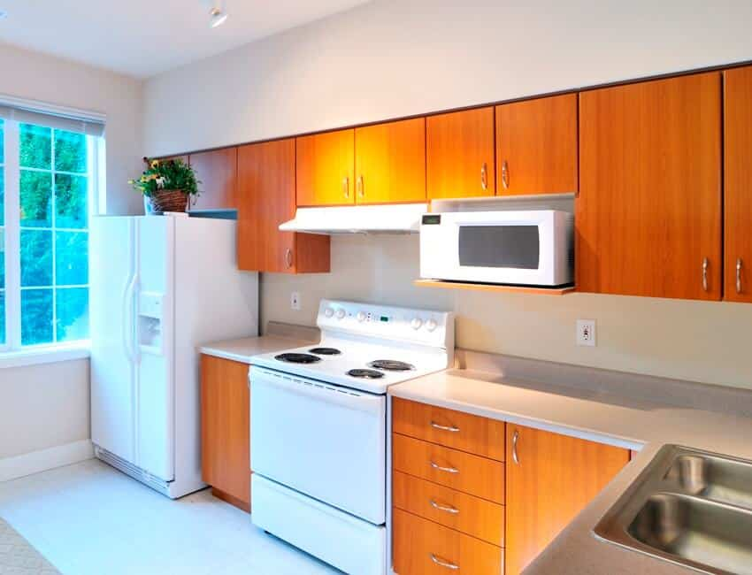 Small space kitchen with an outside view from the window wood cabinets and white appliances