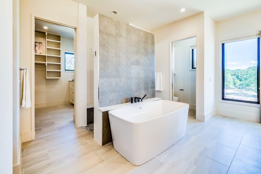 Spacious and bright bathroom bathtub gray wall glass window