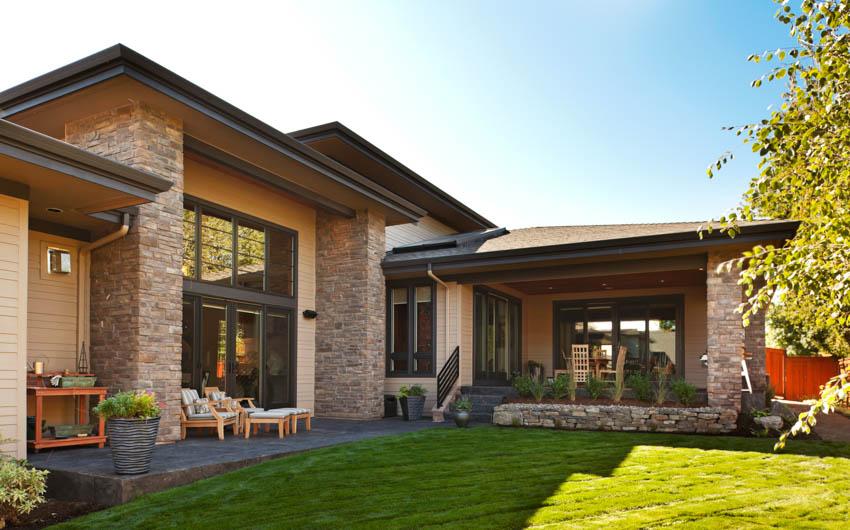 Spacious backyard lawn brick wall house