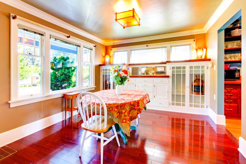 Spacious dining area cherry wood flooring windows