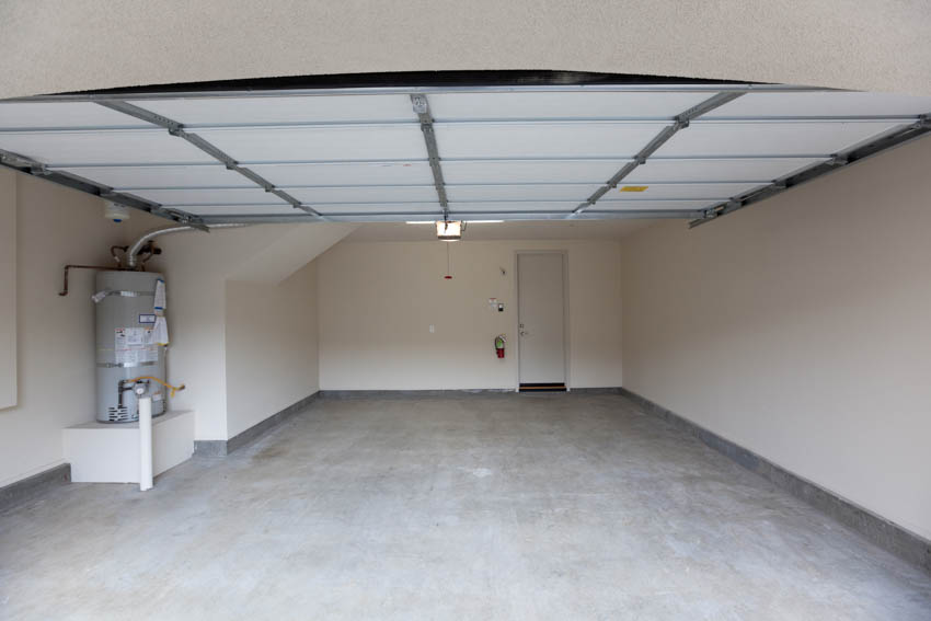 Spacious garage with water heater leading to bathroom