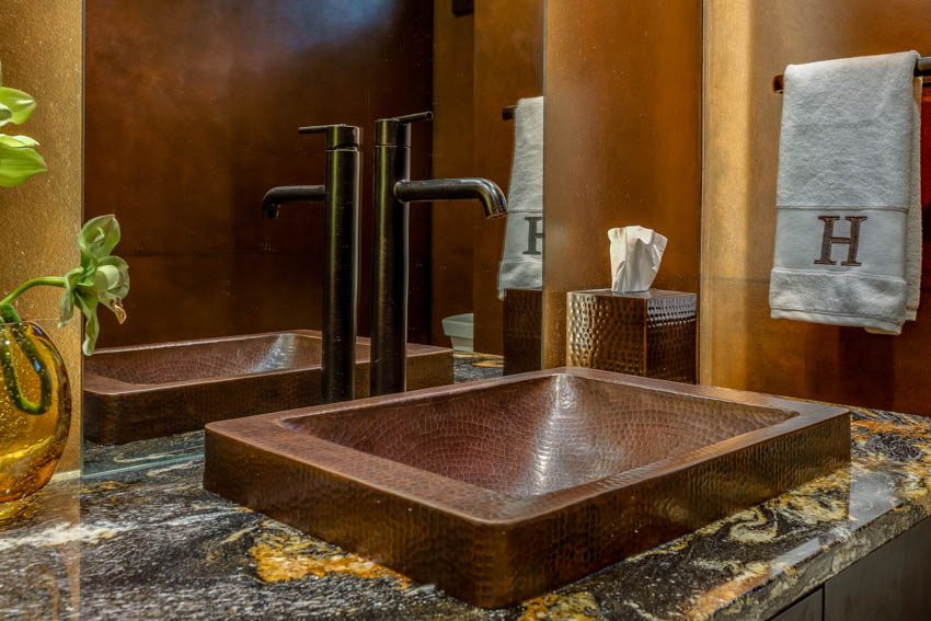 Square shaped copper sink on marble countertop