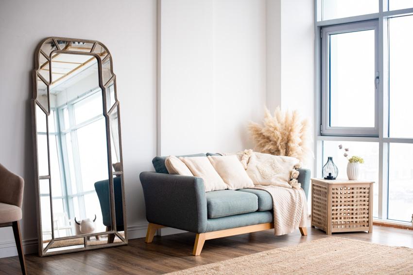 Standing mirror near window sofa chair